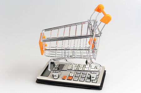 economise: Shopping cart situated on calculator on gray background