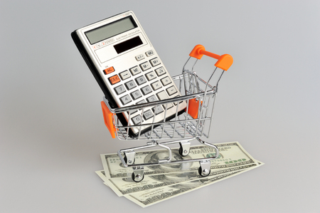 Calculator in shopping cart situated on banknotes on gray background photo