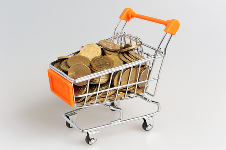 Shopping cart full of coins on gray background photo