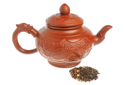 tea kettle: Chinese clay teapot with handful of green tea isolated on white background