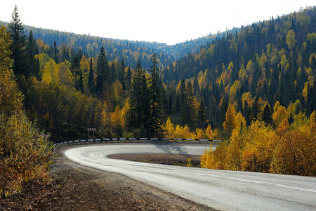 Sharp road bend in autumn ural mountains photo