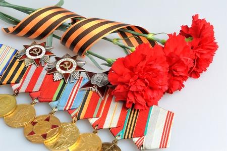 anti fascist: Three red carnations tied with Saint George ribbon and medals with orders on gray