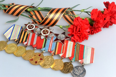 Red carnations tied with Saint George ribbon and medals with orders on gray background photo