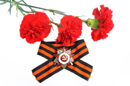 anti fascist: Saint George ribbon with order of the Great Patriotic and red carnations isolated on white Stock Photo