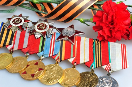 anti fascist: Red carnations tied with Saint George ribbon and medals with orders on gray background closeup