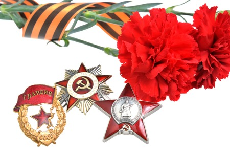Red carnations tied with Saint George ribbon and orders of Great patriotic war isolated on white photo