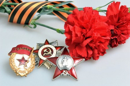 anti fascist: Red carnations tied with Saint George ribbon and orders of Great patriotic war on gray background
