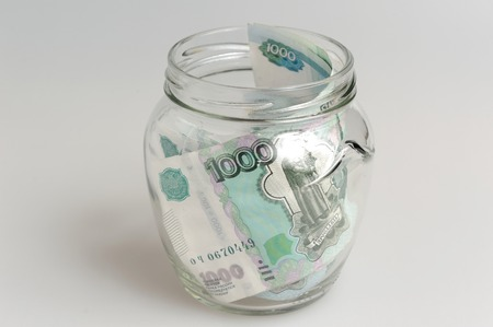 Money in open glass jar on the gray background photo