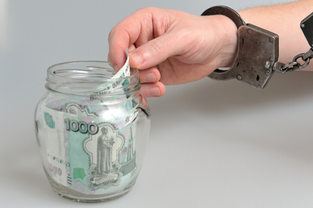 cheater: Hand in handcuffs is taking money from glass jar on gray background Stock Photo