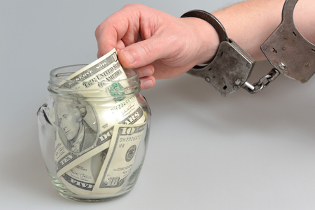 Hand in handcuffs is taking money from glass jar on gray background Stock Photo