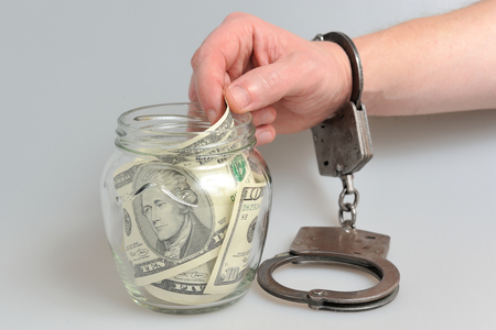 penal: Hand in handcuffs is taking money from glass jar on gray background Stock Photo