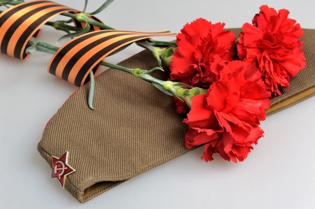 anti fascist: Military cap and red carnations tied with Saint George ribbon on gray