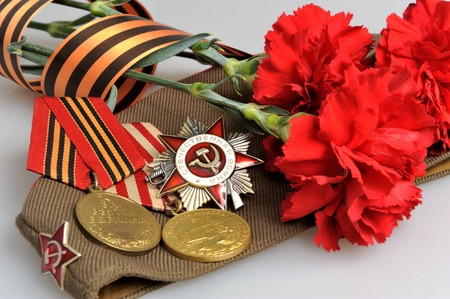 Soviet military cap with red flowers, Saint George ribbon and medals of Great Patriotic war on gray photo
