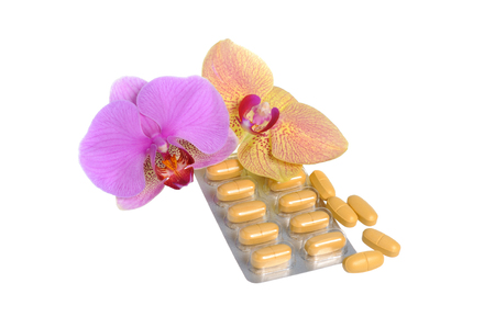 gynecologic: Film-coated tablets with two orchid flowers isolated on white Stock Photo