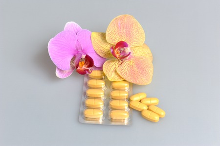 gynecologic: Film-coated tablets with two orchid flowers on gray background Stock Photo
