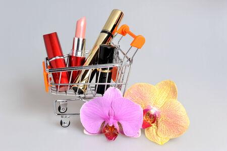 carretilla de mano: Maquillaje en carretilla de mano con flores de orqu�deas en fondo gris