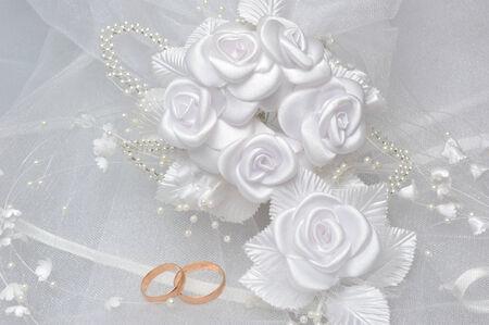 Hochzeitsringe auf Brautschleier mit weißen Ansteckblume auf grauem Hintergrund