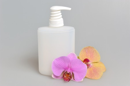 Intimate gel or liquid soap dispenser pump plastic bottle orchid flowers on gray background Stock Photo