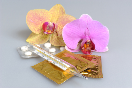 condones: Comprimidos recubiertos con pel�cula, condones y term�metro con dos flores de orqu�deas de color gris
