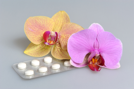 gynecologic: Two orchid flowers with film-coated tablets on gray background