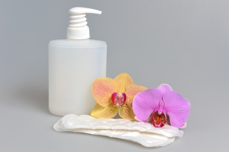 sanitary towel: Intimate gel dispenser pump plastic bottle and sanitary towel with orchid flowers on gray Stock Photo
