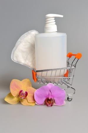 carretilla de mano: �ntimo botella de pl�stico de la bomba dispensador de gel y la toalla sanitaria en carretilla de mano con flores de orqu�deas de color gris