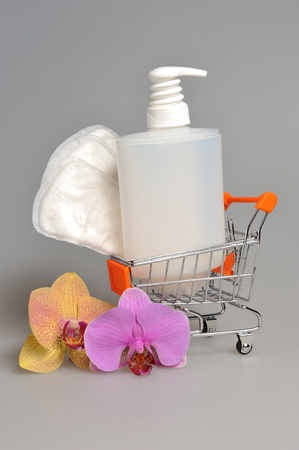 sanitary towel: Intimate gel dispenser pump plastic bottle and sanitary towel in pushcart with orchid flowers on gray