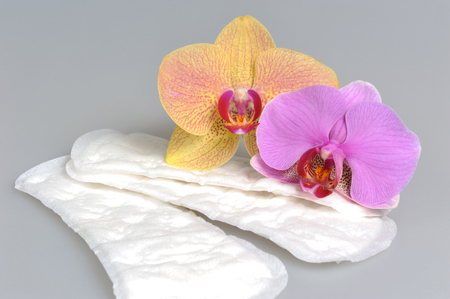 Sanitary towels with orchid flowers on gray background photo