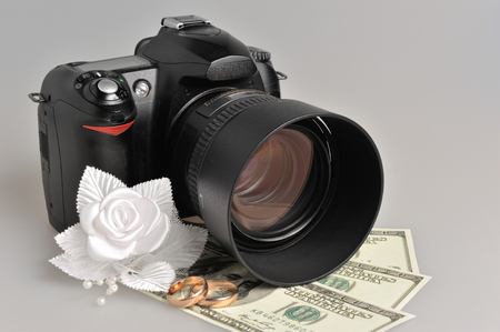 Photo camera, wedding boutonniere, rings with money on gray background