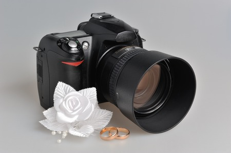 Photo camera, wedding boutonniere, rings on gray background