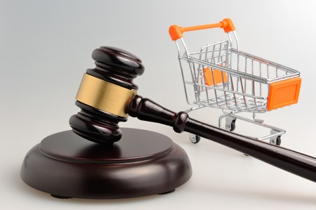 Hammer of judge and pushcart on gray background photo