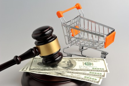 consumer rights: Hammer of judge, pushcart and money on gray background