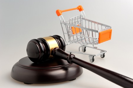 consumers: Hammer of judge and pushcart on gray background