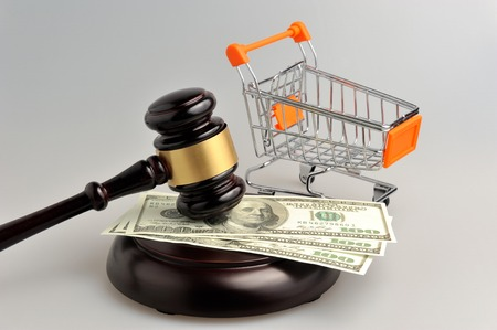 consumer rights: Hammer of auctioneer with pushcart and money on gray background