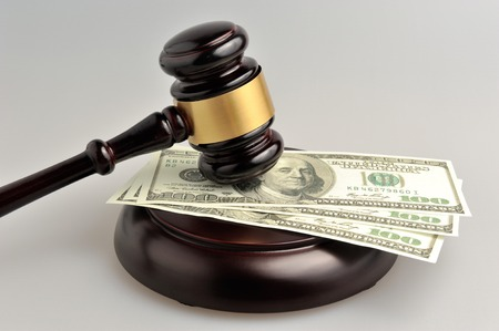 juror: Hammer of judge with money on gray background Stock Photo