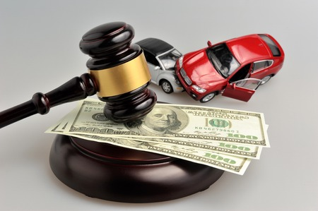 灰色の背景にお金とおもちゃの車と裁判官のハンマー 写真素材