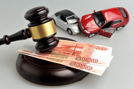 Hammer of judge with money and toy cars accident on gray background Stock Photo
