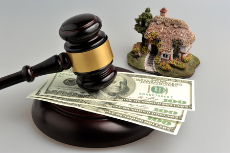Hammer of judge with dollars and model of house on gray background photo