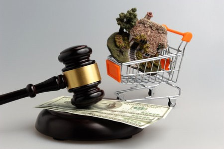 Hammer of judge with dollars and model of house in trolley on gray background