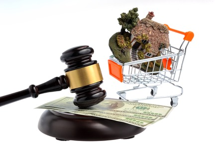 Hammer of judge with dollars and model of house in trolley isolated on white