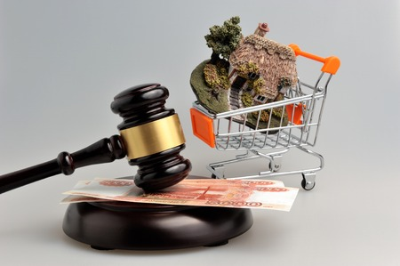 Hammer of judge with money and model of house in trolley on gray background Stock Photo