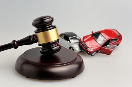 灰色の背景に自動車事故のモデルと裁判官のハンマー