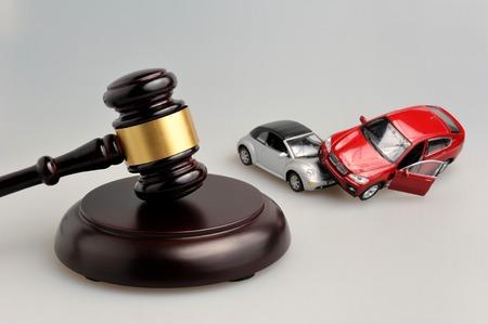 martillo juez: Martillo de juez con los modelos de accidente de coche en el fondo gris
