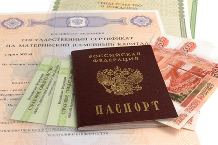 maternal: Russian passport with money and maternal, birth and pension certificates isolated on white