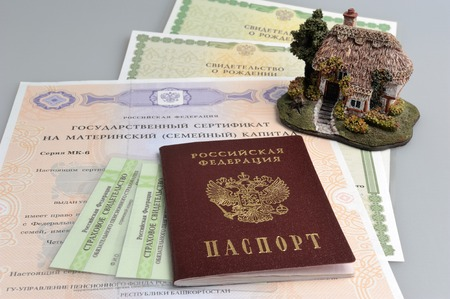 Russian passport with model of house and maternal, birth and pension certificate on gray
