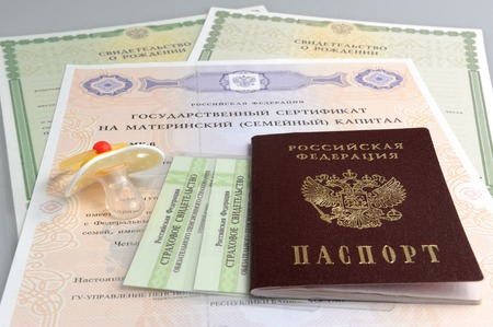 maternal: Russian passport with baby dummy and maternal, birth and pension certificates on gray Stock Photo