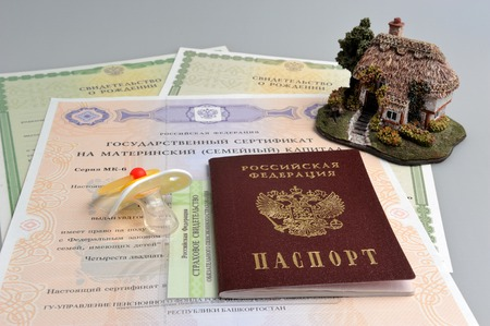 Russian passport with baby dummy, model of house and maternal, birth and pension certificates