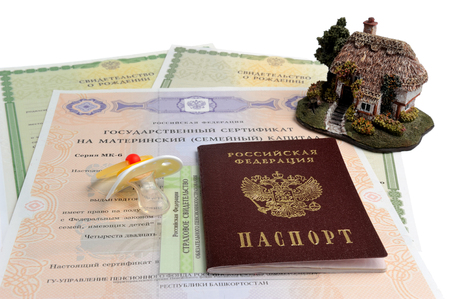 Russian passport with baby dummy, model of house and maternal, birth and pension certificates isolated on white Stock Photo