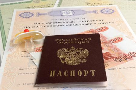 Passport with baby's dummy, money, maternal, birth certificates