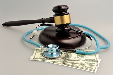 Stethoscope with judge gavel, money on gray
